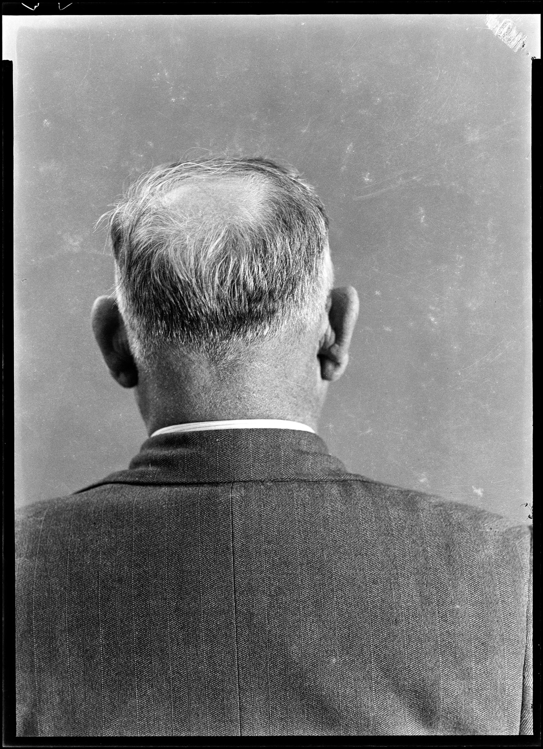 Cellulose negative in loose files, portrait of bald man from rear, location unknown.