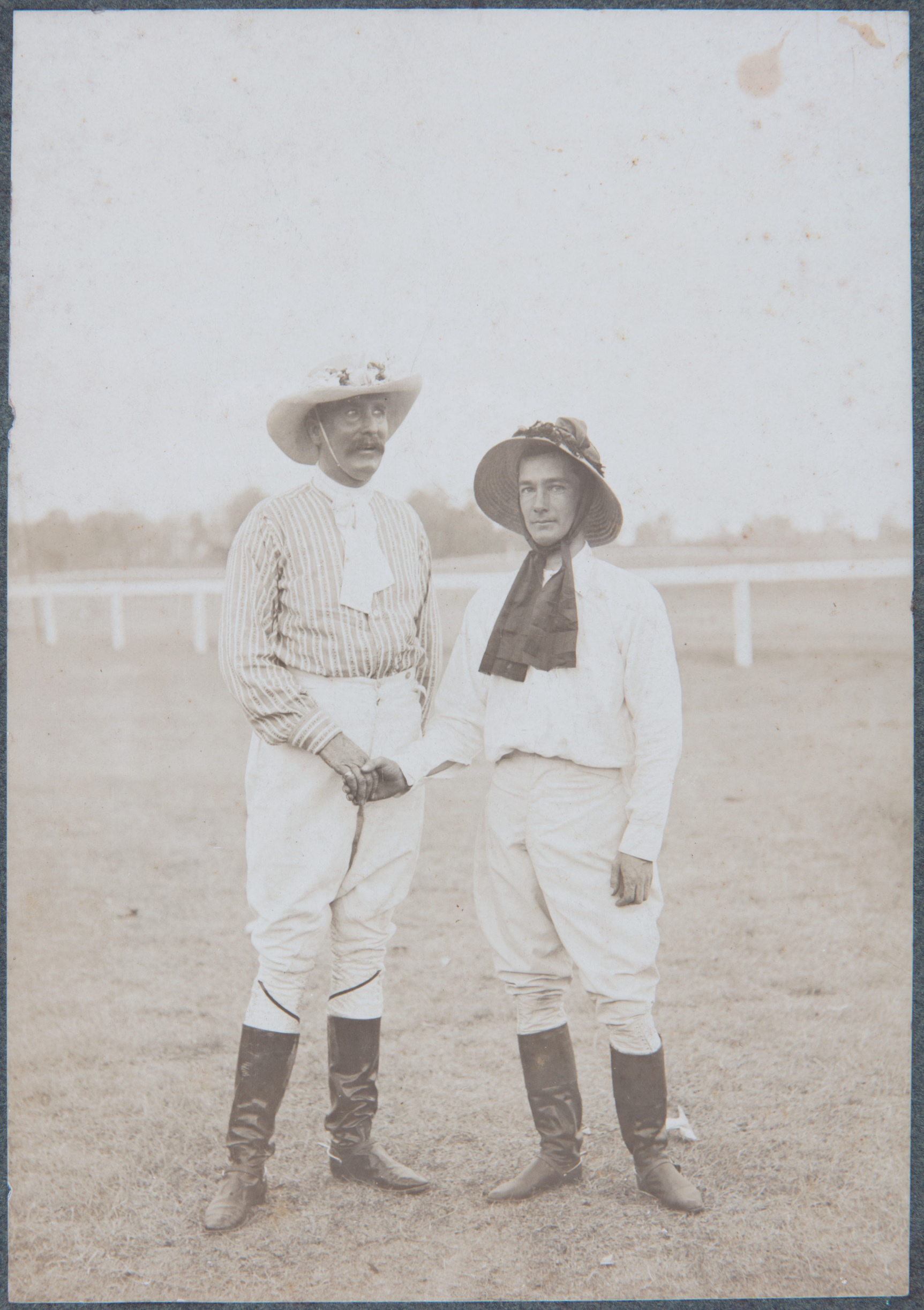 Photograph of George Terry (left) and Norman Pearce wearing ladies' hats for a novelty race at Hawkesbury Racecourse around 1910 / photographer unknown